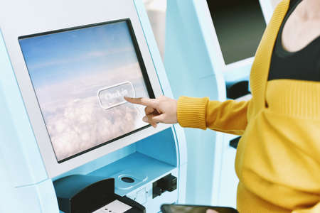 Traveler using a self check-in machine kiosk service at airport, Close up of finger point on display, Technology and smart application to confirm flight booking details, Travel concept.