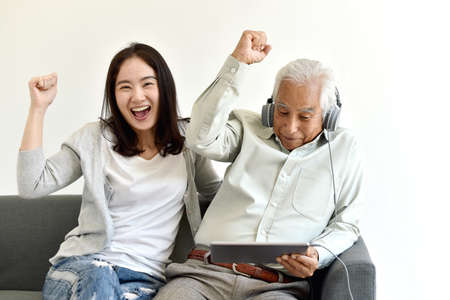 Happy family time, Smiling asian daughter and elderly father enjoy watching movie from laptop computer together, Senior people and social media lifestyle concept.