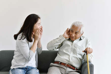 Hearing loss problem, Asian old man with hand on ear gesture trying to listen shouting woman, Aging senior decline in hearing ability, Elderly health problems concept.