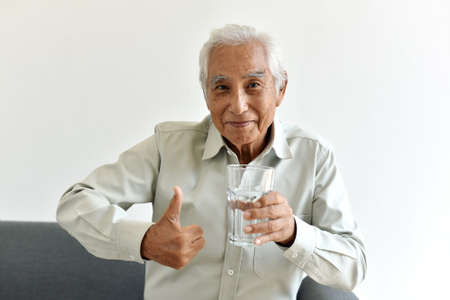 Drinking water is good healthy habit for old man, Elderly smiling asian man show thumb up to glass of purified water, Senior healthcare concept.