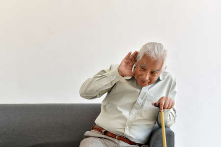 Hearing loss problem, Asian old man with hand on ears gesture trying to listen, Aging senior decline in hearing ability, Elderly health problems concept. 免版税图像