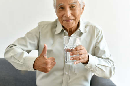 Drinking fresh water is good healthy habit for old man, Elderly smiling asian man show thumb up to glass of purified water, Senior healthcare concept.