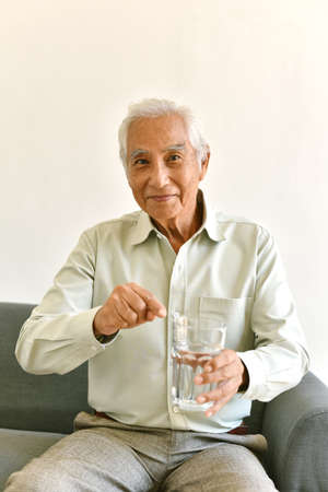 Drinking water is good healthy habit for old man, Elderly smiling asian man pointing at glass of purified water, Senior healthcare concept.