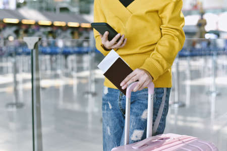 Passenger checking flight status and make a self check-in on smartphone at the airport, Traveller waiting for boarding call at terminal. Tourist arrive at destination, Travel concept. Stock Photo