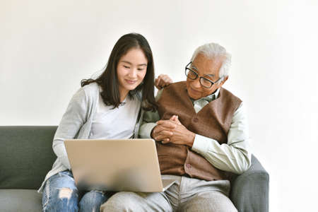 Daughter and elderly father using laptop computer together, Senior people spend time learning to use social media and digital technology platform, Asian family relationship.