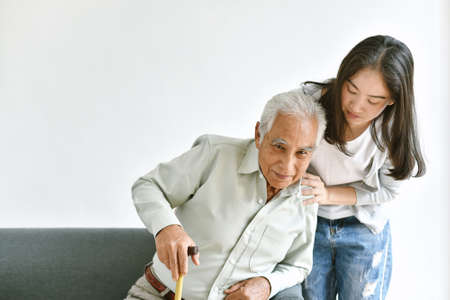 Disable and injury senior asian man try to stand up with walking cane, Knee pain and joint disease in old man, Elderly health problems and insurance concept.