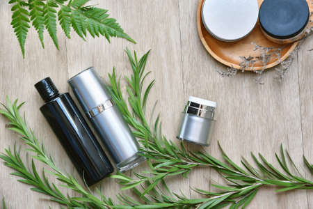 Cosmetic bottle containers packaging with green herbal leaves, Blank label for organic branding mock-up, Natural skincare beauty product concept. Banco de Imagens
