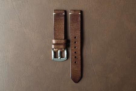 Bracelet de montre en cuir marron foncé avec boucle en acier inoxydable sur fond de cuir, bracelet de montre artisanal et fait main, style classique et vintage de luxe. Banque d'images