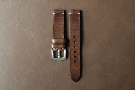 Dark brown leather watch strap with stainless buckle on leather background, Craft and handmade watch bracelet, Luxury classic and vintage style. 免版税图像
