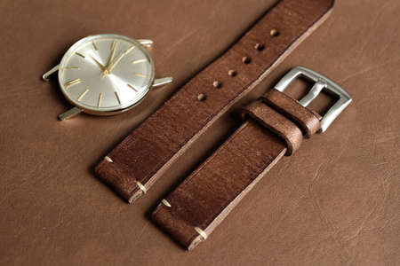 Dark brown leather watch strap with stainless buckle on leather background, Craft and handmade watch bracelet, Luxury classic and vintage style.