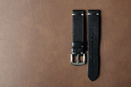 Black leather watch strap with stainless buckle on leather background, Craft and handmade watch bracelet, Luxury classic and vintage style.