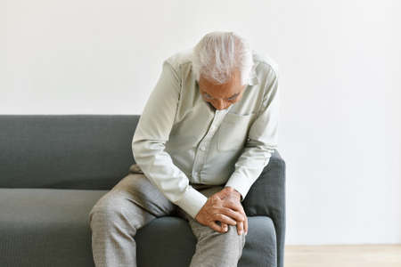 Arthritis joint pain problem in old man, Elderly asian man with hand on knee gesture, Senior suffering and worry about injury symptom, Healthcare insurance concept.