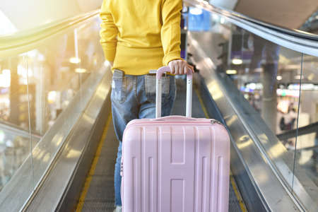 Traveler carry big suitcase on escalator walkway at the airport terminal, Passenger walking with luggage to departure check-in counter, Tourist arrive at destination, Travel concept.