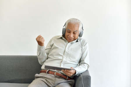 Senior old people and social media lifestyle concept, Smiling elderly father enjoy watching movie from laptop computer, Old man using digital technology.