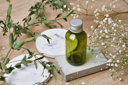 Cosmetic bottle containers packaging with green herbal leaves, Blank label for organic branding mock-up, Natural skincare beauty product concept. Imagens