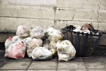 Garbage bags from household wet food trash, Waste separation management problem in urban, Pile of rubbish on city footpath street.