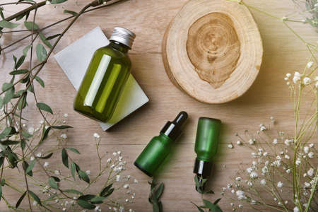 Cosmetic bottle containers packaging with green herbal leaves, Blank label for organic branding mock-up, Natural skincare beauty product concept. Stock fotó