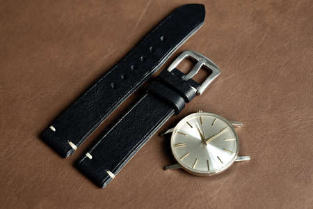 Vintage wristwatch on a brown leather background. Classic watch straps, Genuine handcraft italian calfskin leather with white top stitching.