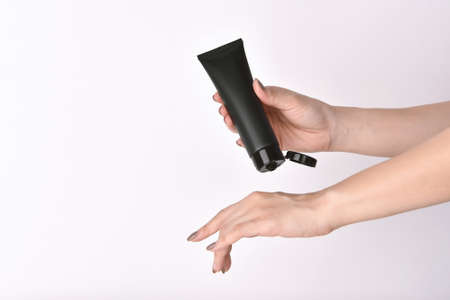 Hands applying skincare moisturizer. Woman holding a cosmetic bottle containers, Blank label for beauty product branding mock-up.