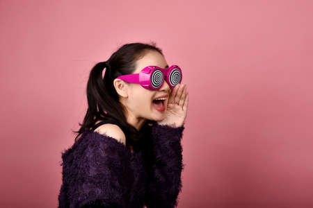 Surprised asian woman, Shouting girl wearing funny glasses on isolated pink background, Wow face feelings with copy space for advertising. Reklamní fotografie