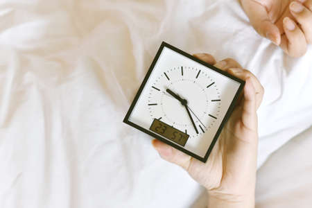 Sleepy girl's hand showing alarm clock and waking up late in the morning, Woman sleep in and laying down in bed hiding under the blanket, Sleep disorder and not enough rest problem. Banco de Imagens