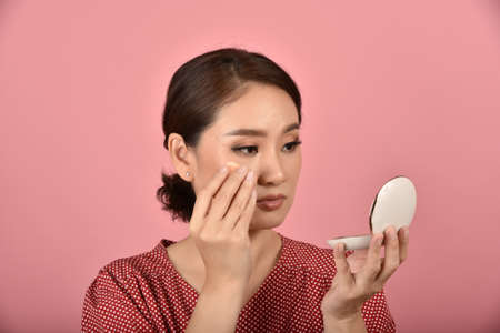 Asian woman looking at her facial problem in the mirror, Female feeling annoy about her reflection appearance show the aging skin signs, Makeup cover skin problem.