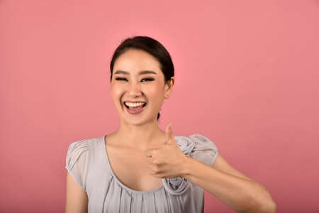 Asian woman showing thumb up gesture, Happy smiling cheerful girl doing like symbol, Face expression.