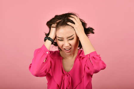 Angry asian woman, Screaming girl with furious aggressive hand gesture on pink background, Face expression and human emotion.