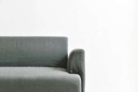 Gray fabric sofa on white wall, Minimal and simple living room interior with copyspace. Foto de archivo