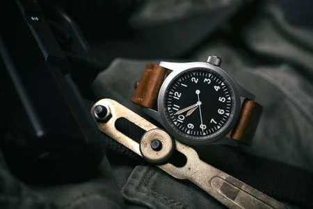 Field watch vintage style, Military wristwatch with leather strap and pistol. Classic mechanical timepiece, Men fashion and accessories.