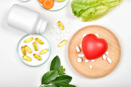Vitamin nutrition pills and heart model, Natural medicine supplement from organic fresh fruit and vegetable, Healthy beauty food diet. Standard-Bild