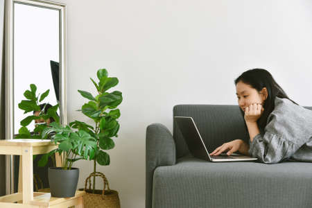 Woman working from home by laptop computer surround green tropical tree, Human and nature, Houseplants growing in living room for indoor air purification and home decorative.