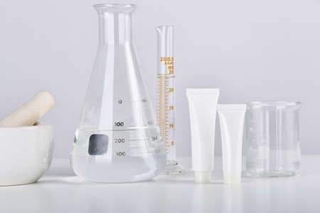 Cosmetic bottle containers and scientific glassware, Blank package for branding mock-up, Pharmaceutical skincare by dermatologist doctor, Research and develop beauty product concept. Imagens