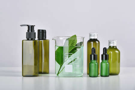 Natural skincare beauty product research, Organic botany extraction in scientific glassware at science laboratory, Blank cosmetic bottle container for branding mock-up.