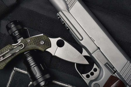 Weapons and military equipment for army, Semi-automatic handgun .45 pistol tactical flash light and pocket army knife. Фото со стока