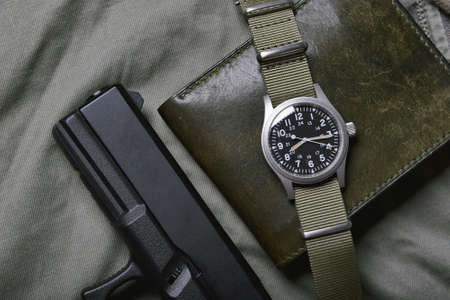 Vintage military watch with nato strap and pistol on army green background, Classic timepiece mechanical wristwatch, Military men fashion and accessories.