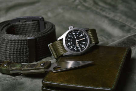 Vintage military watch with nato strap and tactical knife on army green background, Classic timepiece mechanical wristwatch, Military men fashion and accessories. Imagens
