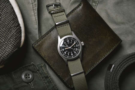 Vintage military watch with nato strap and leather wallet on army green background, Classic timepiece mechanical wristwatch, Military men fashion and accessories.
