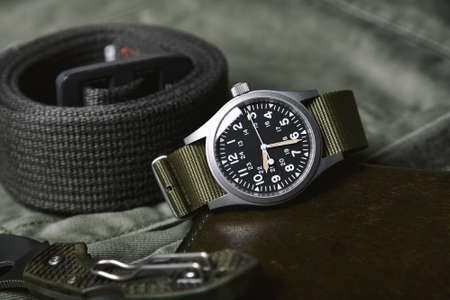 Vintage military watch and tactical belt on army green background, Classic timepiece mechanical wristwatch, Men fashion and accessories.