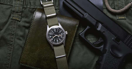 Vintage military watch wallet and pistol on army green background, Classic timepiece mechanical wristwatch, Military men fashion and accessories.