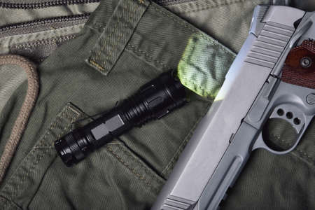 Weapons and military gun equipment for army with tactical flashlight, Semi-automatic 1911 model handgun, .45 pistol on green military uniform background. Imagens