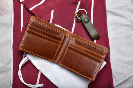 Genuine leather wallet, Handcraft full grain brown bifold wallet on shirt background, Men fashion and accessory. Imagens