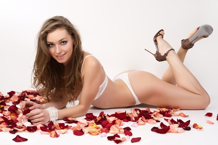 hand bra: Portrait of beautiful young woman lying in rose petals.