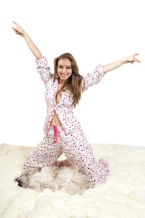 Picture of a morning sweet young girl in pink pajamas. Women with dog. photo