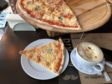 Pizza with cheese and coffee in a white mug in a cafe top view
