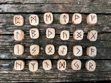 A stack of wooden runes at forest. Wooden runes lie on a old wood background. Runes are cut from wooden blocks. On each rune symbol for fortune telling is designated. Zdjęcie Seryjne