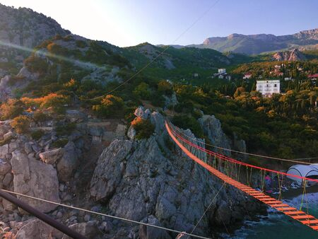View of suspension red rope bridge in mountain