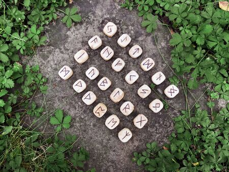 A stack of wooden runes at forest. Wooden runes lie on a rock background in the green grass. Runes are cut from wooden blocks. On each rune symbol for fortune telling