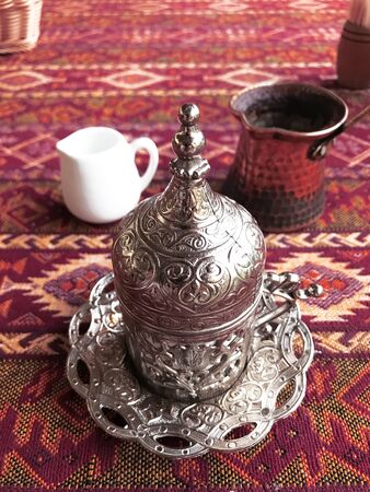Turkish coffee in metal cup with ornaments on red  Zdjęcie Seryjne