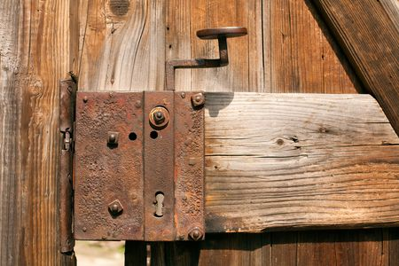 old rusty door lock on an ailing wooden gate photo